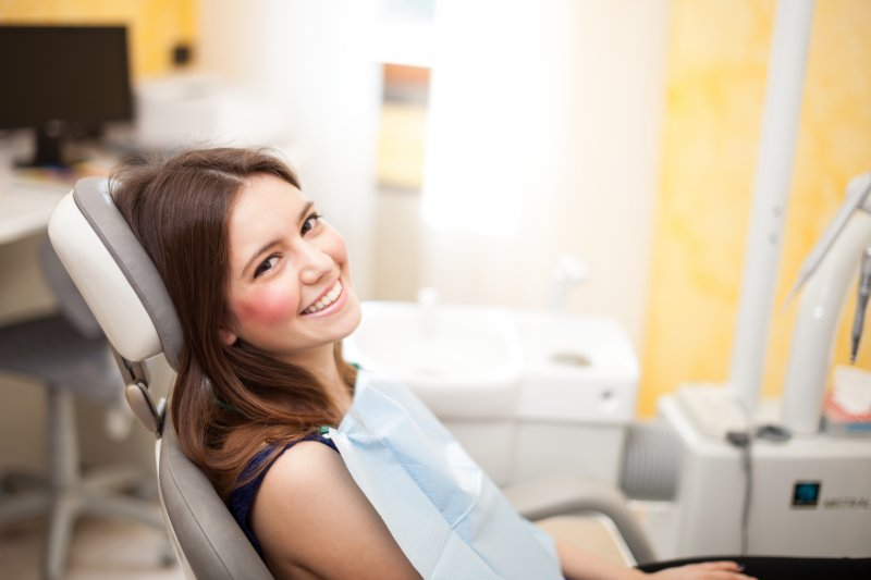 woman smiling sitting in dentist chair