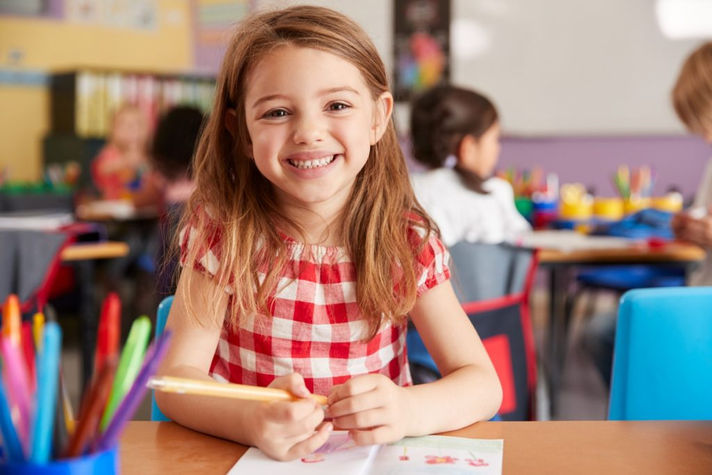 Child smiling while completing activity in classroom